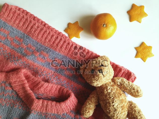 Children's sweater and a toy bear, tangerines on a white background - Free image #198785