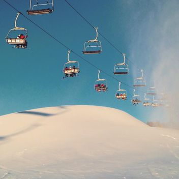 Snowy ski lift against the sky lifts skiers on the mountain - image #198835 gratis