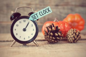 Black alarm clock with text reset clocks, pine cones and pumpkins on wooden background - Kostenloses image #271595