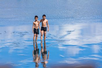 Two boys walking in water - бесплатный image #273605