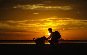 silhouette of man and dog at sunset - image #303985 gratis