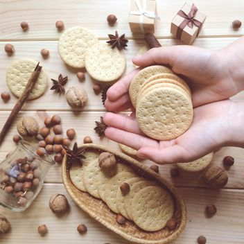 cookies in hands, nuts and anise on wooden background - бесплатный image #329135