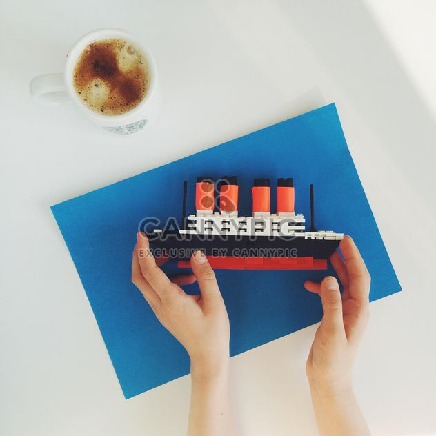 Toy ship in hands and cup of coffee - Free image #329165