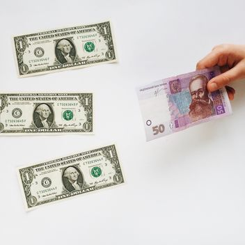 American money on the table and Ukrainian money in hand on a white background - бесплатный image #329225