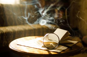 Burning incense sticks and open book through a magnifying glass - бесплатный image #330405