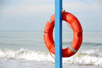 Lifesaver circle hanging on blue pillar - image gratuit #333135