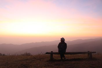 Woman sitting on bench at sunset - image #338505 gratis
