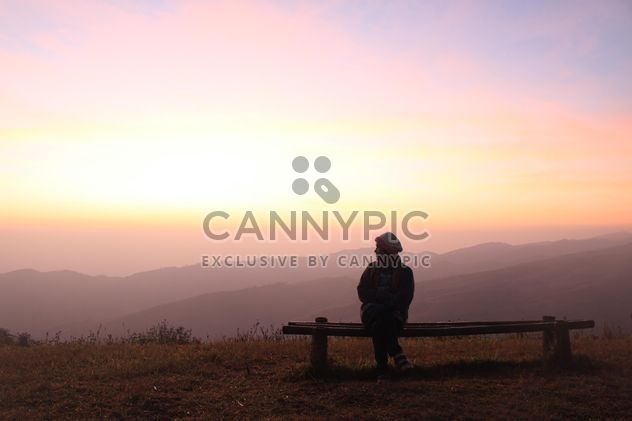 Woman sitting on bench at sunset - Free image #338505