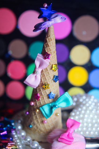 Icecream cone with ribbons and stars on a background of colorful eyeshadow palette - Free image #341495