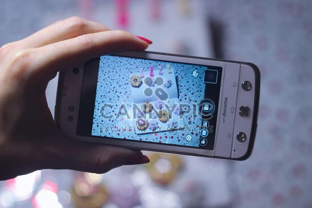 Smartphone decorated with tinsel in woman hands - Free image #342185