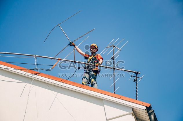 Worker installing antenna on roof top - Free image #344535