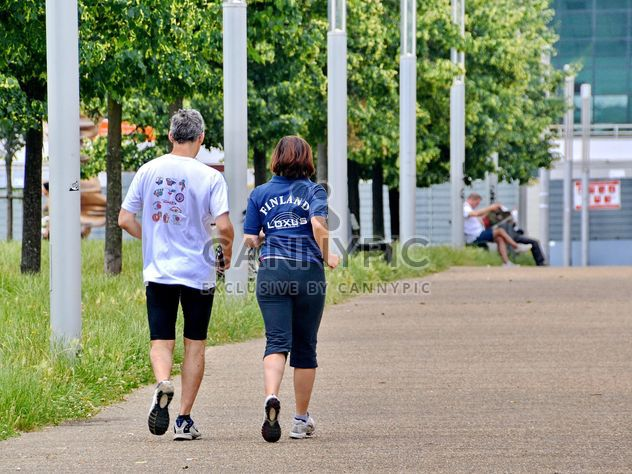 Rear view of senior couple jogging in park - Kostenloses image #344565