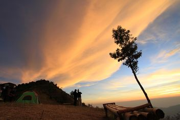 Tourists near tent under cloudy sky at sunset - Kostenloses image #344605