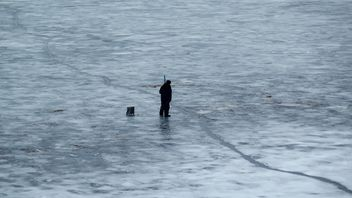 Fisherman during winter fishing on frozen river - Free image #344625