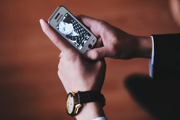 Closeup of smartphone in male hands - image #345885 gratis