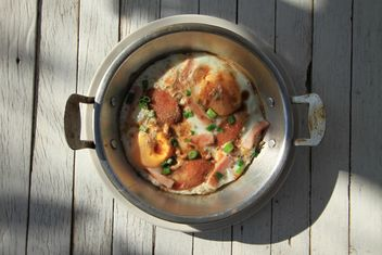 Fried eggs with sausage and green onion in pot - image #346975 gratis