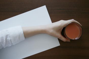 Glass of juice in hand on wooden table - image #348675 gratis