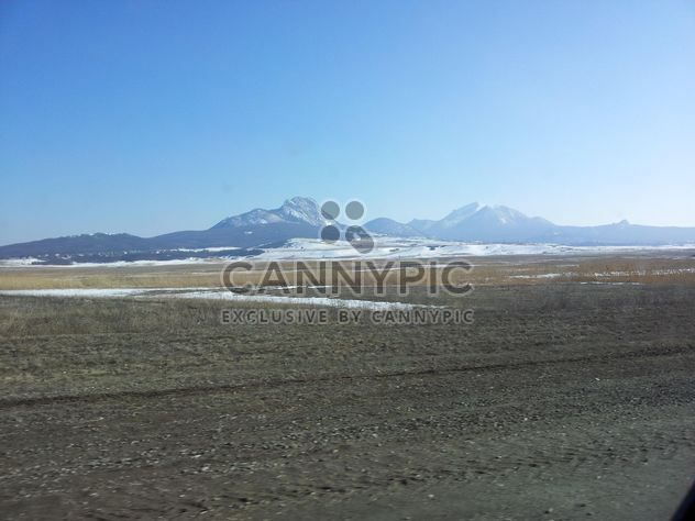 Mountains with snow in winter against the blue sky near the frozen lake - Free image #350205