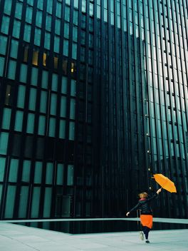Woman with orange umbrella on a background of modern building facade - бесплатный image #439115