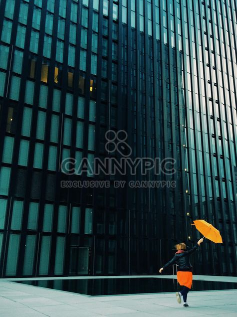 Woman with orange umbrella on a background of modern building facade - Free image #439115