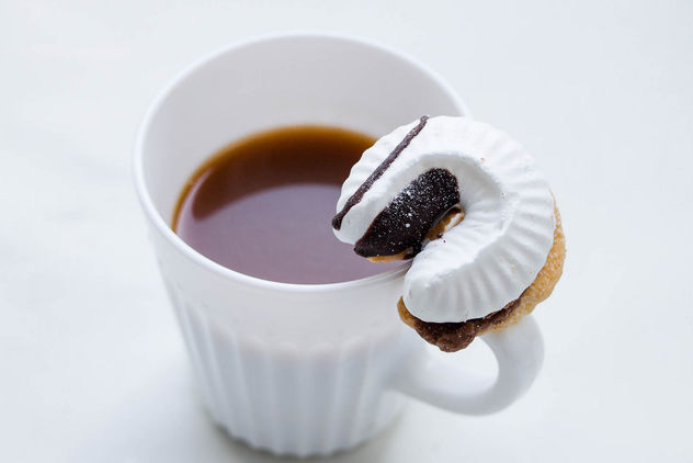A cup of coffee and a cookie with a cream - Free image #449145
