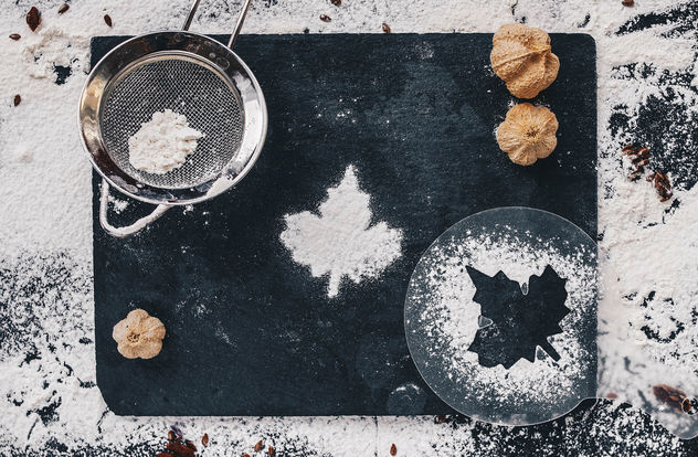 Baking backround with flour and leaf shape on black kitchen table. Top view.jpg - image gratuit #450725