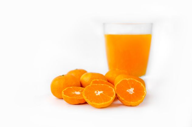 orange juice in glass on white background - image #452525 gratis