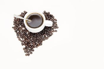 cup of coffee and coffee beans laid out in the shape of heart - image #452565 gratis